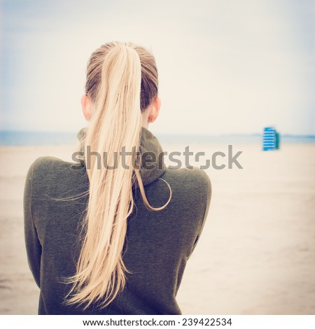Lonely girl with long blond ponytail at empty foggy beach. Selective focus. Image with filter effect instagram - stock photo