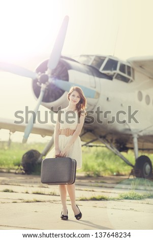 Lonely girl with suitcase at near airplane. Photo in old image style.