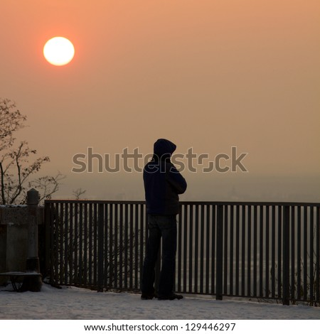 Lonely guy standing below a clear sunset, watching the scenery of Karlsruhe, Germany