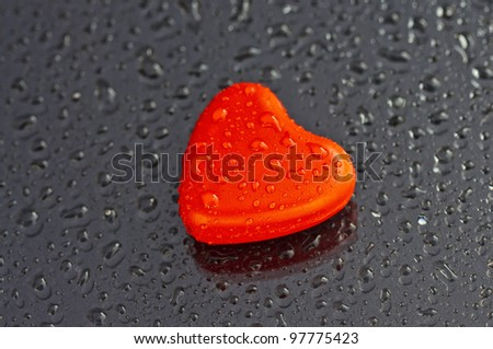 Lonely heart in grey background with water drops