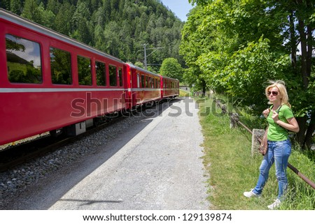 Lonely hiker looking at the Swiss mountain Train  Bernina Express - stock photo