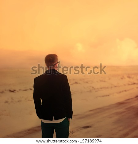 lonely hipster guy looks at the sunset - stock photo