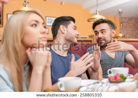 Lonely in the crowd. Friends having brunch in the cafe while handsome guys talking their female friend is getting bored - stock photo