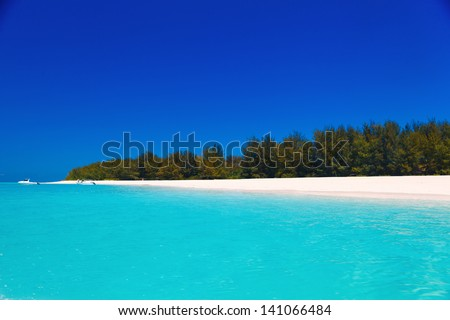 lonely island in crystal clear water - stock photo