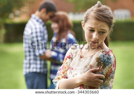 Lonely Jealous Teenage Girl With Romantic Couple In Background - stock photo