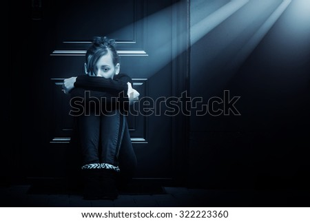 Lonely lady sitting at the doorstep in the spotlight. - stock photo