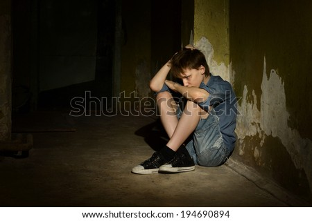 Lonely little boy in a dark cellar - stock photo