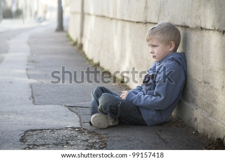 Lonely little boy sits at pathway - stock photo
