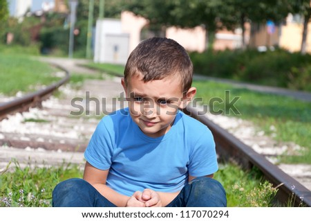 lonely little boy sitting on a rails - stock photo