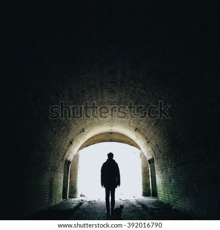 lonely man hipster sihouette and cat on tunnel in the dark dungeon - stock photo