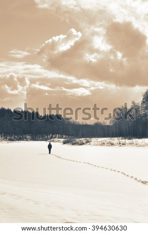 Lonely man in the snow looking at the clouds. Special toning. - stock photo