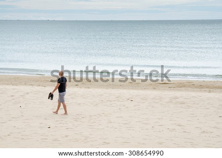 Lonely man relax walking along the sea beach seashore