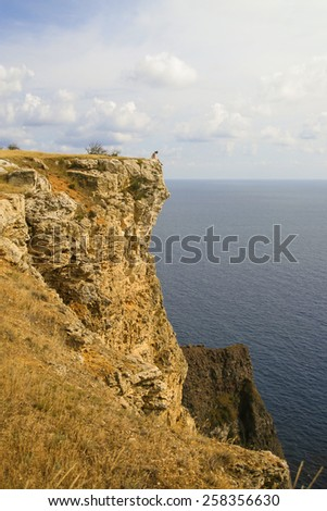 Lonely Man sitting on edge of the cliff in Fiolent cape, Crimea - stock photo