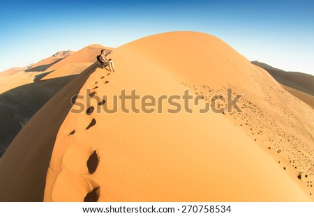 Lonely man sitting on sand at Dune 45 in Sossusvlei - Concept of wanderlust in namibian famous desert - Adventure trip travel to african wonders in Namibia - Composition with fisheye lens distortion - stock photo