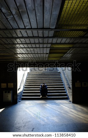 Lonely man sitting on the stairs - stock photo