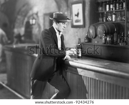 Lonely man standing at a bar counter with a drink - stock photo