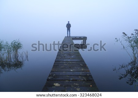 Lonely man standing on a jetty at a lake during a foggy, gray morning. - stock photo