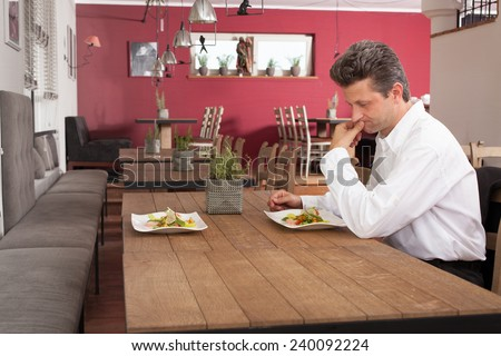 Lonely man waiting for dinner - stock photo