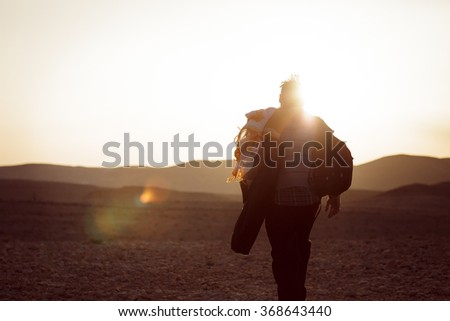 Lonely man walking in the Negev desert in Israel with strong sunset back light. Color toned image. Hiker walk in a hot stone desert. - stock photo