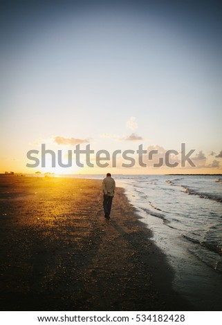 lonely man walking on the beach at sunset.