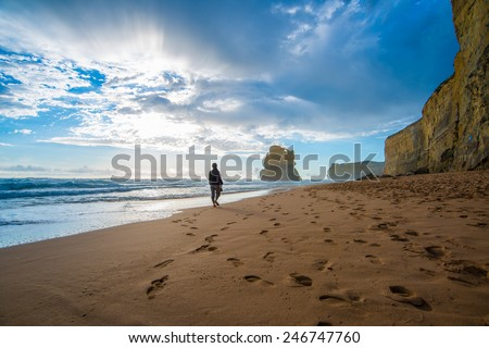 Lonely man walking on the beach leaving footprints - stock photo