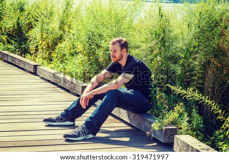 Lonely man with beard, mustache thinking outside. sitting on wooden road with high grasses, wearing black v neck T shirt, blue jeans, sneakers, relaxing, waiting for you. Instagram effect.