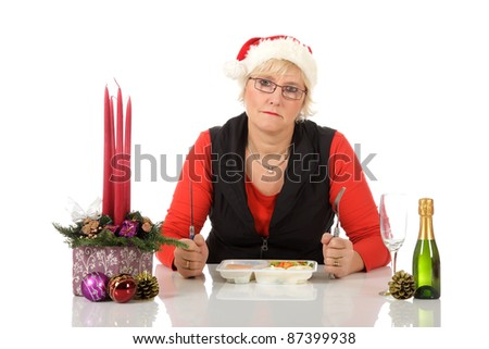 Lonely middle aged caucasian woman with Santa hat, sitting at table with microwave food. Sad Christmas dinner. Studio shot. White background.