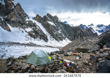 Lonely mountaineers camp in very high snowy moutains beside glacier. Picture was taken during a trekking hike in the amazing and stunning Caucasus mountains, Bezengi region, Kabardino-Balkaria, Russia - stock photo