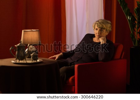 Lonely old lady spending whole evening on recalling the past - stock photo