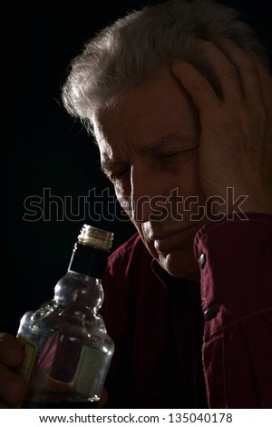 lonely old man drinking alcohol on a black background