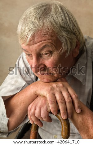 Lonely old man in nursing home leaning on his cane