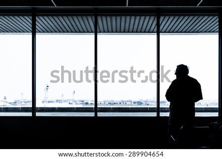 Lonely old man waiting for flight aircraft  - stock photo