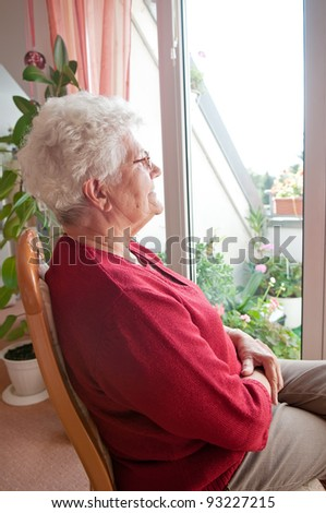lonely old woman looks out the window - stock photo