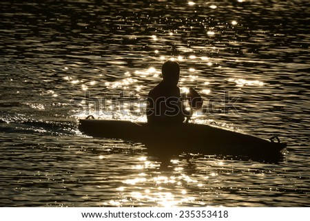 Lonely paddler on the lake during the sunset - stock photo