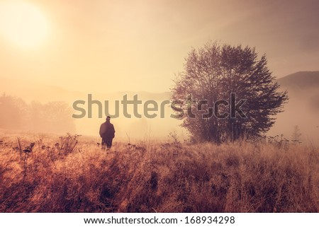 Lonely person in the morning mist. Landscape composition. - stock photo