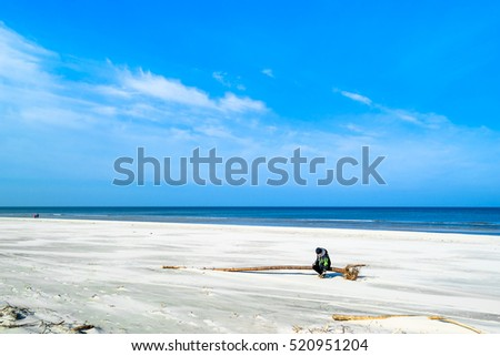 Lonely person in winter clothing. Man on the beach over sea, landscape