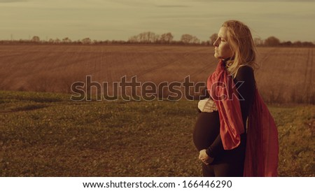 Lonely pregnant woman standing in a field worried about her future - stock photo