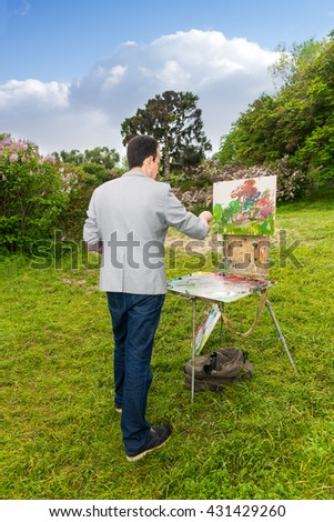 Lonely professional male artist  working outdoors in the park  on a trestle and easel painting with oils and acrylics during an art class - stock photo