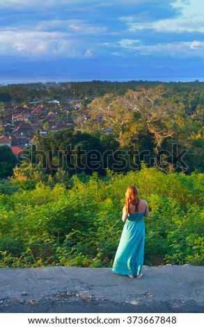 Lonely red-haired girl at sunset - stock photo