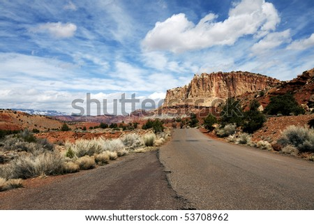 Lonely Road in Capitol Reef Looking Back at Butte and a Very Dramatic Blue Sky - stock photo