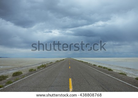 Lonely road one point perspective highway yellow stripes against blue gray storm horizon travel trip - stock photo