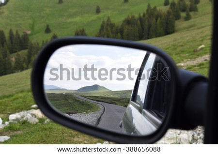 Lonely road seen through rear mirror - stock photo