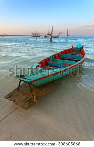 lonely rowing boat at sunset - stock photo