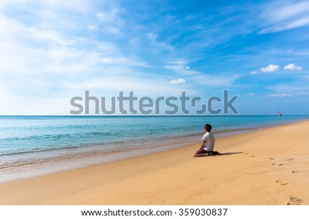 lonely sad man sitting on a beautiful deserted beach and looking into the distance at sea