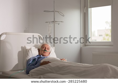 Lonely sad terminally ill patient in hospital bed - stock photo