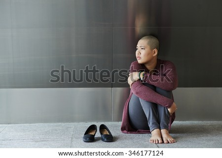 Lonely sad woman sitting on the floor - stock photo