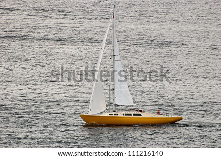 Lonely sailboat in the Baltic Sea. Shot at sunset. - stock photo