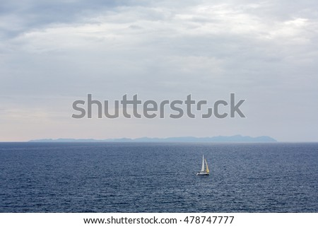 Lonely sailboat in the sea with Majorca landscape in the background