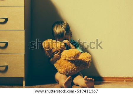 Lonely scared boy sitting in corner, hugging his teddy bear and crying. Child abuse