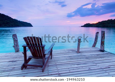 Lonely scene ; Single wooden chair in the port over sea at twilight - stock photo